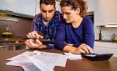 stock photo of accountability  - Serious young couple reviewing their bank accounts with a digital tablet and calculator at home. Financial family concept.