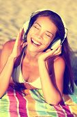 picture of singing  - Woman listening to music with headphones at beach - JPG