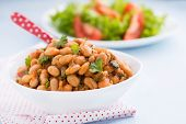 picture of stew  - Stewed white beans with tomato sauce and parsley in white bowl close up selective focus - JPG