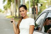 picture of key  - Young adult hispanic woman holding keys of new white car leaning on auto door - JPG