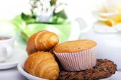 picture of continental food  - continental breakfast with croissants cake chocolate cookies and tea - JPG
