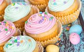 foto of easter candy  - Pastel Easter cupcakes with candy and sprinkles on green wooden vintage background shallow depth of field - JPG