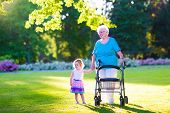 picture of retirement age  - Happy senior lady with a walker or wheel chair and a little toddler girl grandmother and granddaughter enjoying a walk in the park - JPG