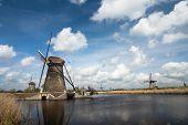 stock photo of windmills  - Traditional dutch windmill near the canal - JPG