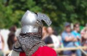 stock photo of battlefield  - Medieval Knight with iron helmet looks at the battlefield