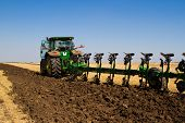foto of tractor  - Agricultural tractor plowing a field before sowing - JPG