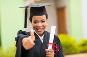 picture of graduation  - beautiful african female graduate giving thumb up at graduation ceremony - JPG