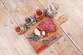 stock photo of peppercorns  - raw beef meat fillet with peppercorn and thyme and different spices in glass bottles ready to grill on wood figured aged board over table - JPG
