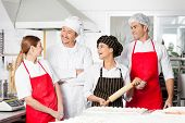 foto of conversation  - Cheerful male and female chefs conversing while preparing pasta in commercial kitchen - JPG