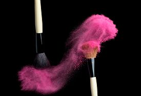 stock photo of face-powder  - Make up brush with pink   powder splash isolated on black - JPG