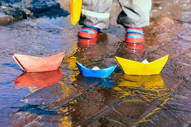 picture of boat  - child playing with paper boats in spring water puddle - JPG