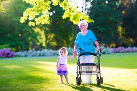 stock photo of grandparent child  - Happy senior lady with a walker or wheel chair and a little toddler girl grandmother and granddaughter enjoying a walk in the park - JPG