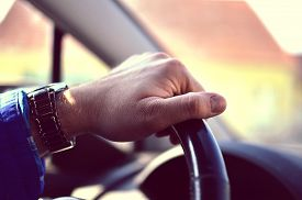 stock photo of designated driver  - Male driver hands holding steering Wheel and driving  - JPG