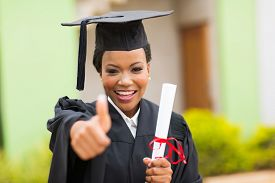 stock photo of graduation gown  - beautiful african female graduate giving thumb up at graduation ceremony - JPG