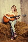 picture of denim jeans  - Beautiful girl teenager in shirt and torn jeans playing guitar sitting on hay - JPG