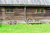 pic of wagon wheel  - Four wagon wheels leaning against an old wooden farm building made of timber - JPG