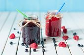 image of mason  - Tasty berries jam in mason jar on light wooden table with fresh raspberries and blueberries - JPG