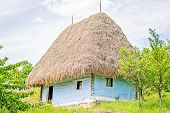 pic of stone house  - Light blue old clay house with a thatched roof exposed wooden beams and stone foundation - JPG
