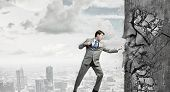 picture of karate  - Businessman breaking stone wall with karate punch - JPG