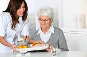stock photo of 70-year-old  - Beautiful nurse bringing meal tray to old woman at nursing home - JPG