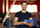 Portrait of personal trainer holding clipboard with training plan in gym poster