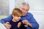 stock photo of grandpa  - Old man with little boy playing video game on telephone - JPG