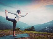 Woman doing yoga asana Natarajasana - Lord of the dance pose outdoors at waterfall in Himalayas. Vin poster