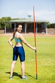 Постер, плакат: Portrait of female athlete standing with javelin in a stadium
