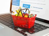 Shopping basket with variety of grocery products ion laptop keyboard. E-commerce concept 3d illustra poster