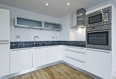 contemporary white kitchen with built in appliances and mosaic tiles