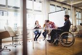 Coworker on wheelchair with photo editors in meeting room at creative office poster