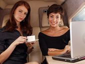 Two women working inside a private jet.