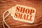 Shop Small - Small Business Saturday concept - a paper price tag with a twine against burlap canvas poster