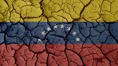 Political Crisis Or Environmental Concept: Mud Cracks With Venezuela Flag poster