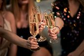 Female Friends Make Toast As They Celebrate At Party. Group Of Partying Girls Clinking Flutes With S poster
