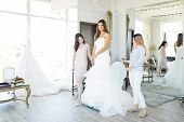Satisfied Hispanic Bride Wearing An Elegant White Dress While Friends Assisting Her In Bridal Store poster