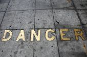 Metal Words in the Sidewalk. Old Metal Words imbedded in cement. The word DANCER written in Brass Le poster