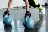 Cropped View Of Sportswoman In Weightlifting Gloves Doing Plank Exercise On Kettlebells At Sports Ce poster