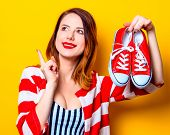 Portrait Of Beautiful Young Smiling Rredhead White Woman In Red Striped Shirt With Gumshoes On Yello poster