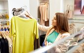 shopping, fashion, sale and people concept - young woman choosing clothes in mall or clothing store poster
