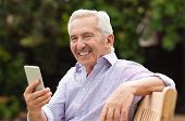Senior man using smartphone while sitting on bench at park. Portrait of handsome old man using smart poster