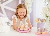 Little pleasured blond girl holding a pink plate looking on sweet cakes on the background of pretty  poster