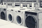 Row of washing mashines in appliance store, toned image poster