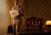 stock photo of mafia  - Retro businessman reading newspaper - JPG