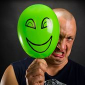 image of angry smiley  - Angry man hiding behind green balloon with happy smiley - JPG