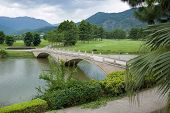 stock photo of cross hill  - Old style stone bridge on a river landscape in a new park in China - JPG