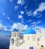Traditional Greek white church arch with cross and bells in village Oia of Cyclades Island Santorini