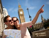 stock photo of lost love  - Happy summer tourists in London holding a map - JPG