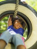 stock photo of tire swing  - Portrait of girl on tire swing - JPG