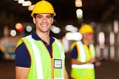 stock photo of vest  - portrait of smiling young warehouse worker indoors - JPG